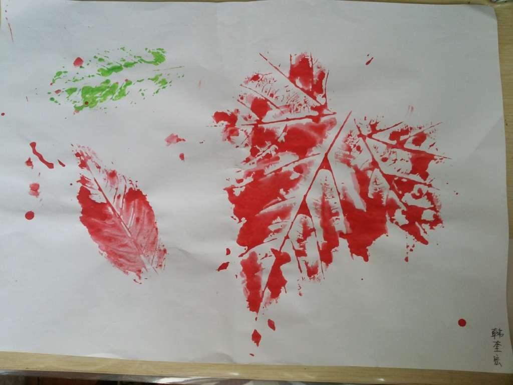 大班的小朋友用捡来的树叶,涂上颜色进行树叶拓印,把秋天的美好记录